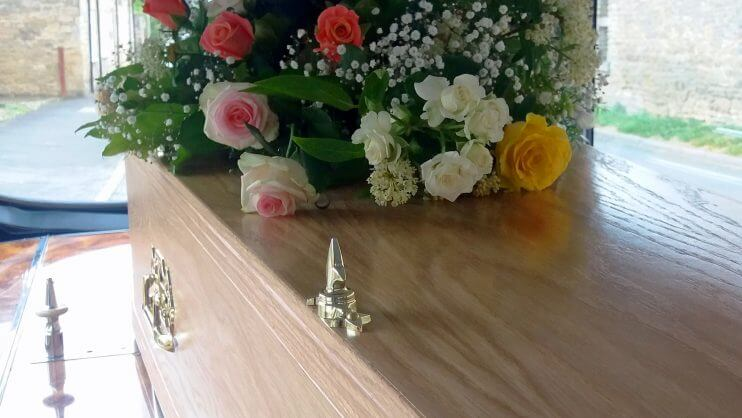 Spray of flowers on top of a coffin